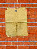 Paper on brick wall. A dirty sheets of paper taped to a brick wall Royalty Free Stock Photography
