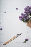 Paper with brushes and bouquet of lilac flowers Stock Images