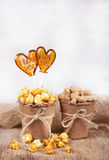 Paper bucket of caramel popcorn and peanuts. Two lollipop in the shape of a heart. Royalty Free Stock Image