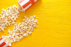 Paper buckets with tasty scattered popcorn on color wooden background