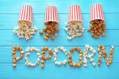 Paper buckets and word made of tasty popcorn on wooden background
