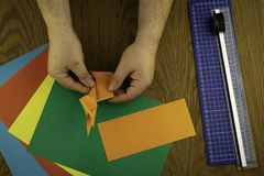 Paper bunny for Easter, hands make origami from colored paper, origami lesson royalty free stock image