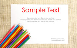 Paper on burlap with pencils & text Royalty Free Stock Photo