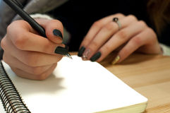 Paper in business woman female hand writing notes on a table black manicure and blank letter. Paper in business woman beautiful female hand writing notes on a stock images