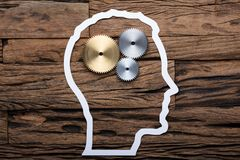 Paper Businessman`s Head Outline With Metallic Gears On Table. Directly above shot of paper businessman`s head outline with metallic gears on wooden table stock photo