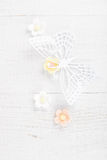 Paper butterfly and three sugar blossom flowers. On white old table Royalty Free Stock Images