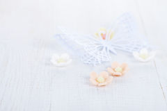 Paper butterfly and three sugar blossom flowers on white old tab Stock Photography