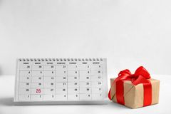 Paper calendar and gift on light background. Christmas countdown. Paper calendar and gift box on light background. Christmas countdown royalty free stock images