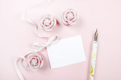 Paper card decorated with pink bow, vintage pen and roses Stock Images