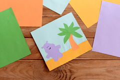 Paper card with happy hippo and a palm tree, colored paper sheets on a wooden table Stock Image
