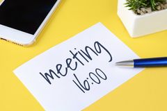 Paper card with. `meeting 16:00` text and pen with phone on a yellow background. Business meetingconcept royalty free stock image