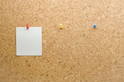 Paper card posted on a cork board with tack pin and waiting pape. R cards for the other tack pins royalty free stock photo