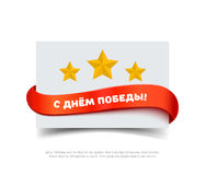 Paper card with red ribbon, yellow stars and inscription in Russian Happy Victory day. Stock Photography