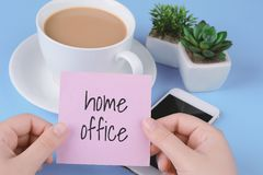Paper card with text. Coffe with phone and paper card with text `home office`on a light blue background royalty free stock image