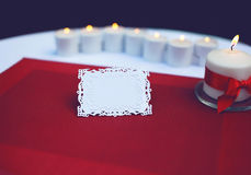Paper card for a text on decorated table with burning candles Stock Photography