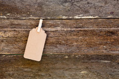 Paper - cardboard label hanging on clothespin against old wooden Royalty Free Stock Photo