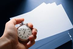 Paper cards and hand with stopwatch stock photo