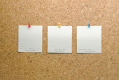 Paper cards posted on a cork board with tack pin. Blank Paper cards posted on a brown cork board with tack pin stock images
