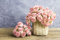Paper carnation in weave basket on old wood Royalty Free Stock Photography
