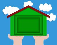 Paper carving of house on the palms against the sky with clouds, ecology idea. Concept of ecological construction. Stock Photo