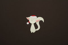 Paper cat applique on texture background. Cute handmade cat in red hat Stock Photos