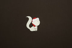 Paper cat applique on texture background. Cute handmade cat in red hats Royalty Free Stock Photo