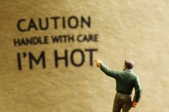 Paper caution label. And miniature figure scene Royalty Free Stock Image