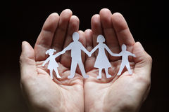 Paper chain family protected in cupped hands. Cutout paper chain family with the protection of cupped hands, concept for security and care Stock Photos