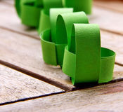 Paper chain. Innd a vibrant green colour on  a wooden backgrou Stock Photography