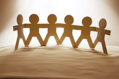 Paper chain team holding hands. Team of paper chain people in a row holding hands Royalty Free Stock Photo