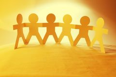 Paper chain team holding hands. Team of paper chain people in a row holding hands Royalty Free Stock Images