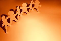Paper chain team holding hands. Team of paper chain people in a row holding hands. Copy space Stock Image