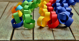 Paper chains. In vibrant colours on a wooden background Royalty Free Stock Photos