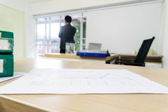 Paper charts on the desk. Paper charts are placed on the table, with the backdrop being a businessman standing looking out the window stock photos