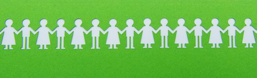 Paper children figurine hold hands on green background stock image