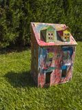 Paper children house made by corrugated fiberboard.Kid toy. Paper children house made by corrugated fiberboard. Kid toy colored and painted with pastels stock photo