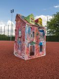 Paper children house made by corrugated fiberboard. Kid toy. Paper children house made by corrugated fiberboard. Kid toy colored and painted with pastels stock photos