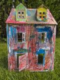 Paper children house made by corrugated fiberboard.Kid toy. Paper children house made by corrugated fiberboard. Kid toy colored and painted with pastels royalty free stock photos