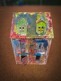 Paper children house made by corrugated fiberboard.Kid toy. Paper children house made by corrugated fiberboard. Kid toy colored and painted with pastels royalty free stock photo