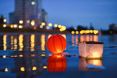 Paper Chinese lanterns floating in river with city lights reflec. Tions  selective focus Royalty Free Stock Photo
