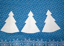 Paper Christmas trees on blue background stock photography