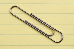 Paper Clip. Closeup image of paper clip on yellow lined paper royalty free stock image