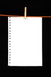Paper clip. White paper with a wooden clip on black background Royalty Free Stock Photos