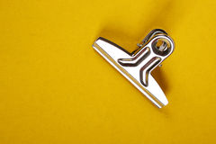 Paper clip. Single bulldog clip isolated on Yellow background Royalty Free Stock Images