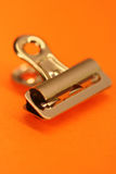 Paper clip. Metallic paper clip on orange background (macro Royalty Free Stock Photo