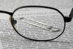 Paper clip and glasses Stock Images