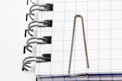 Paper clip  on notebook pages. Isolated over white. Royalty Free Stock Images