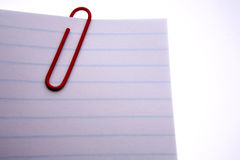 Paper clip with paper. A red paper clip on blue-lined white paper against a white background Royalty Free Stock Images