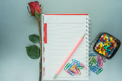 Paper clip, pin and rose. View from above Royalty Free Stock Photography