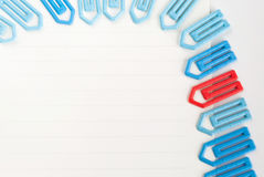 Paper clip on a white paper. Many blue and one red paper clip on a white paper  with space for text Royalty Free Stock Images